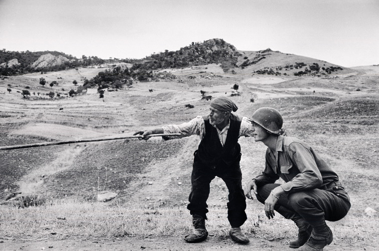 Contadino siciliano indica a un ufficiale americano la direzione presa dai tedeschi, nei pressi di Troina, Sicilia, 4-5 agosto 1943© Robert Capa © International Center of Photography / Magnum Photos