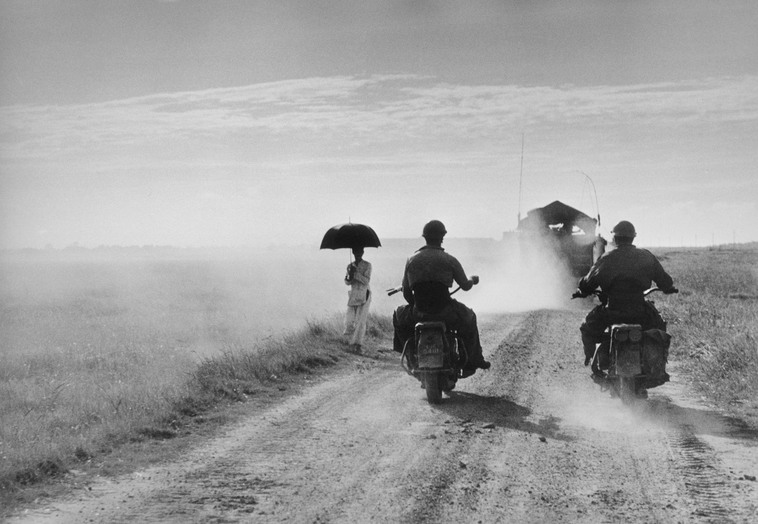 Dei motociclisti e una donna percorrono la strada da Nam Dinh a Thai Binh, Indocina (Vietnam), maggio 1954© Robert Capa © International Center of Photography / Magnum Photos